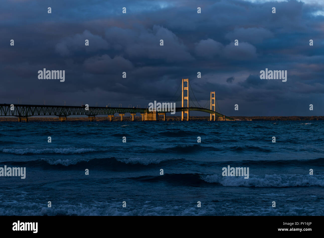 Sunset with stormy clouds light up the Mackinac Bridge spanning the Straits of Mackinac between the upper and lower peninsulas of Michigan, USA. - Stock Image
