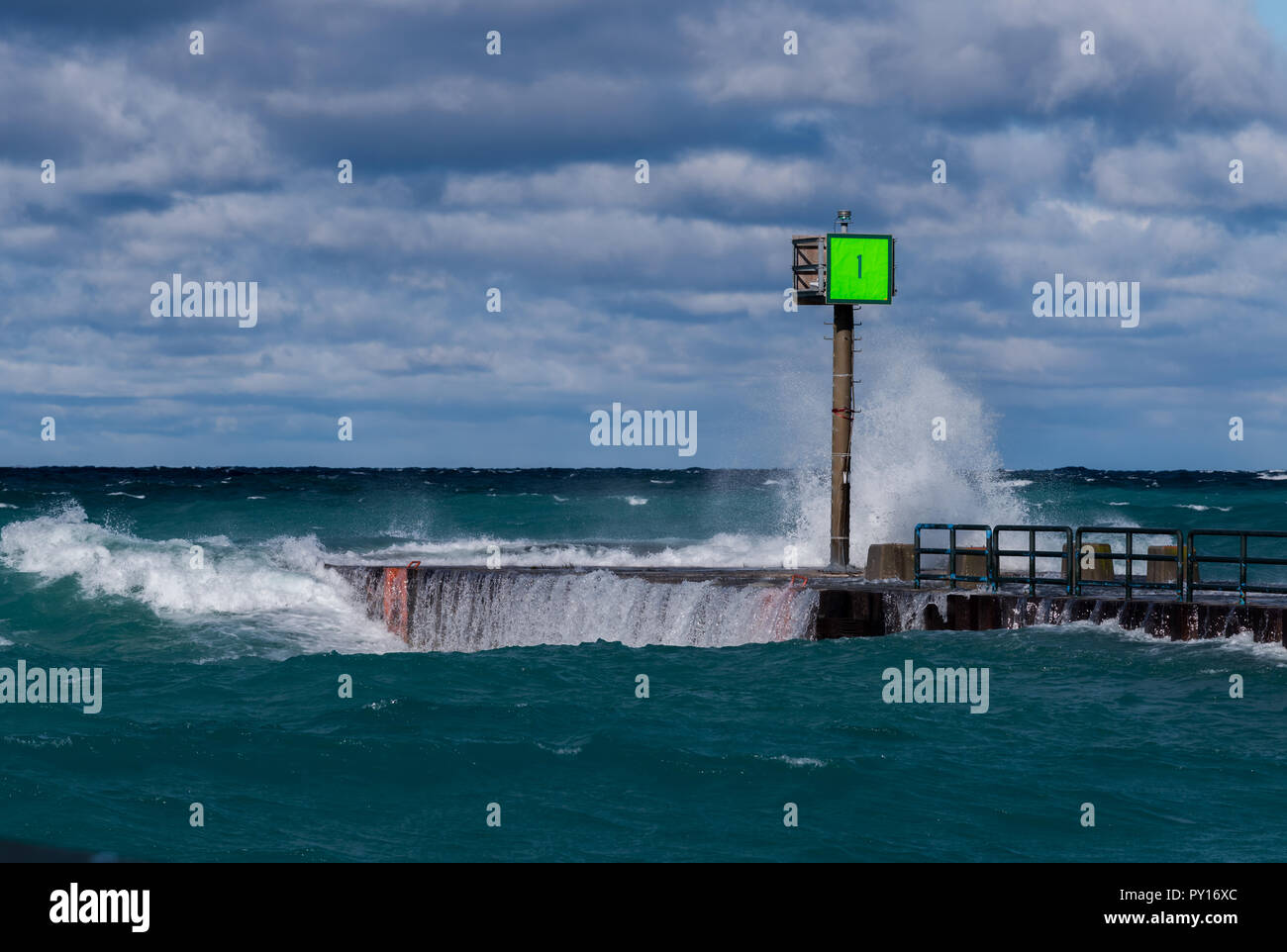 Waves breaking on Marker #1 on the pier in Charlevoix, Michigan, USA. - Stock Image