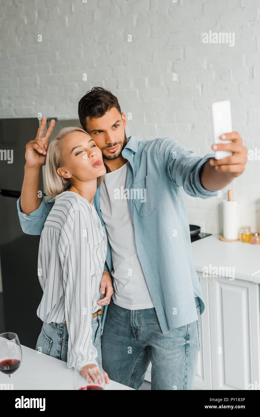 young couple grimacing and taking selfie with smartphone in kitchen - Stock Image
