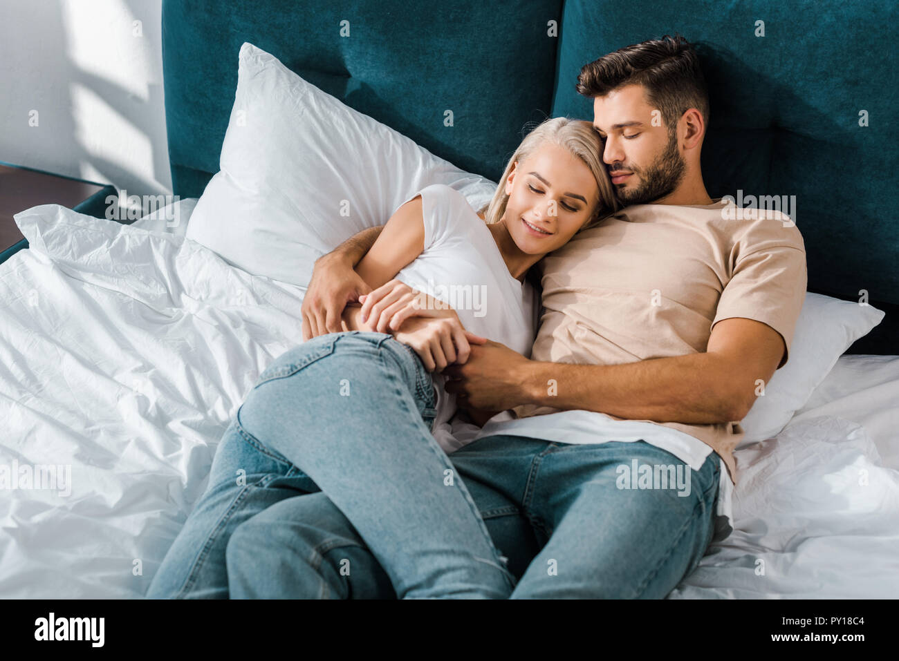 Young Couple Hugging And Sleeping On Bed In Bedroom Stock Photo Alamy