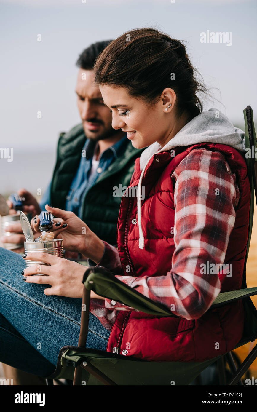 couple eating food from cans while having camping - Stock Image