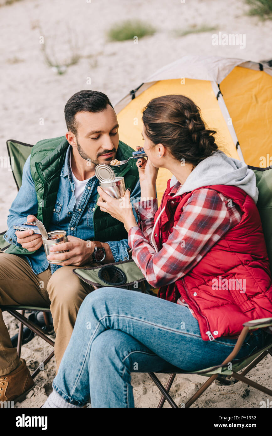 woman feeding husband while having camping together - Stock Image