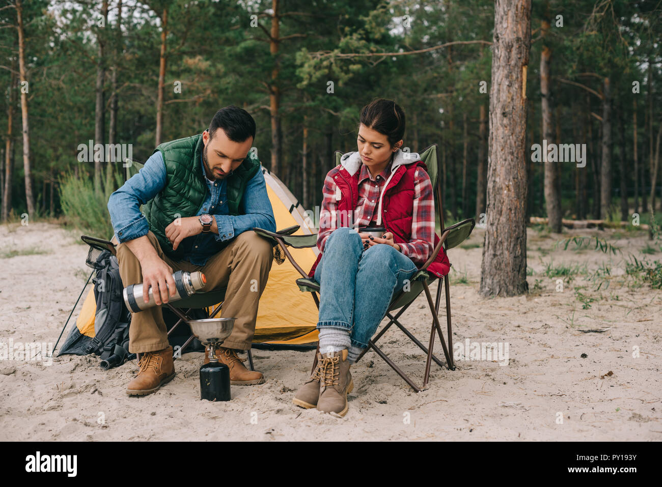 couple having camping on sandy beach with pine forest behind - Stock Image