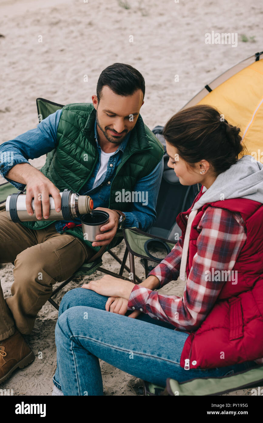 couple drinking hot tea during camping - Stock Image