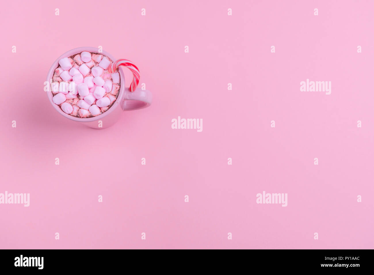 Christmas context in a minimal style with a pink cup of hot chocolate, mini marshmallows and an Xmas candy cane, on a pink paper background. Stock Photo