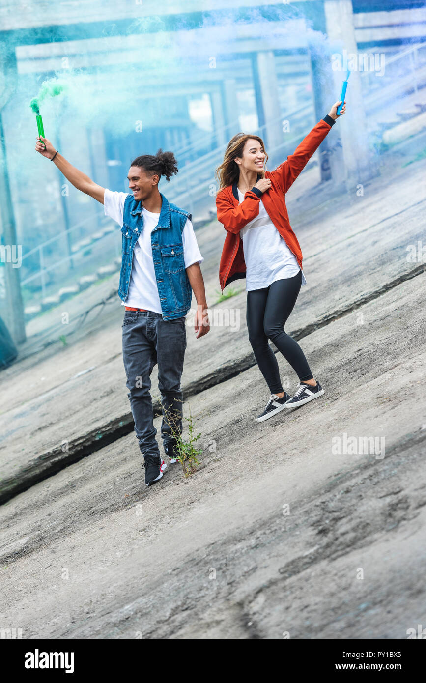 young multicultural couple holding colorful smoke bombs at city street - Stock Image