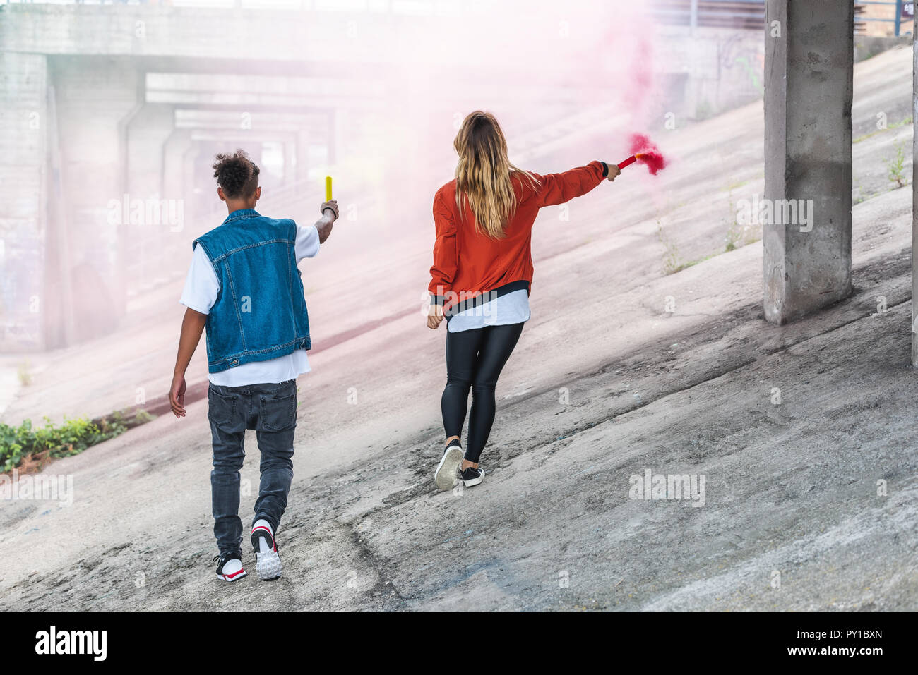 rear view of stylish couple holding colorful smoke bombs at city street - Stock Image