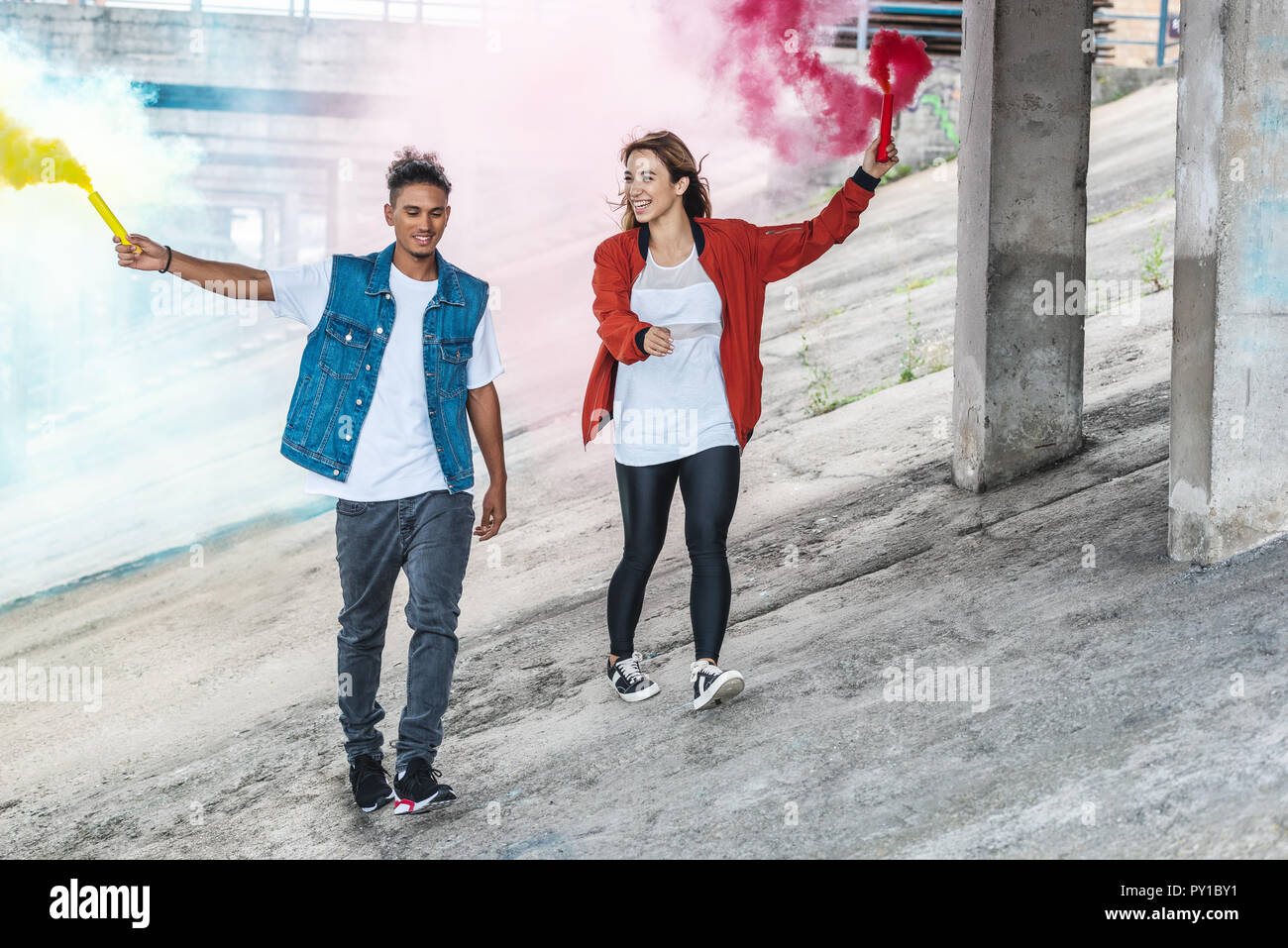 smiling stylish couple holding colorful smoke bombs at city street - Stock Image