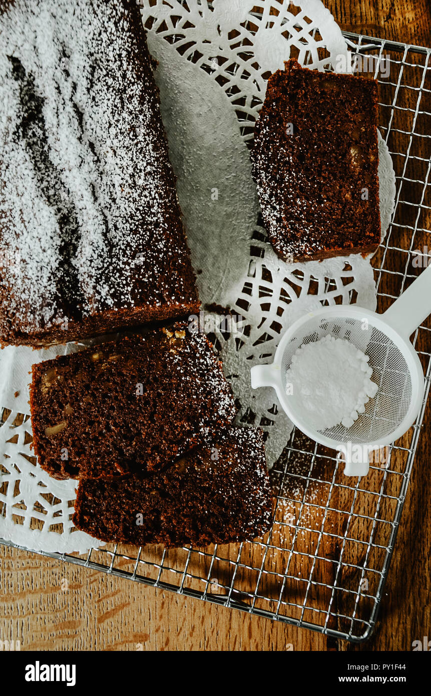 Chocolate cake with nuts inside cut into slices on cooling rack. A mini sieve with powdered sugar. Directly above, wooden table background. - Stock Image