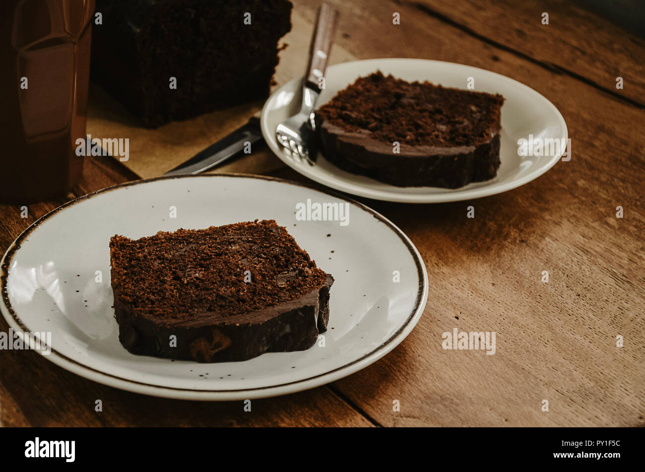 Chocolate pound cake pieces on white plates. Brown toned, wooden background. Stock Photo