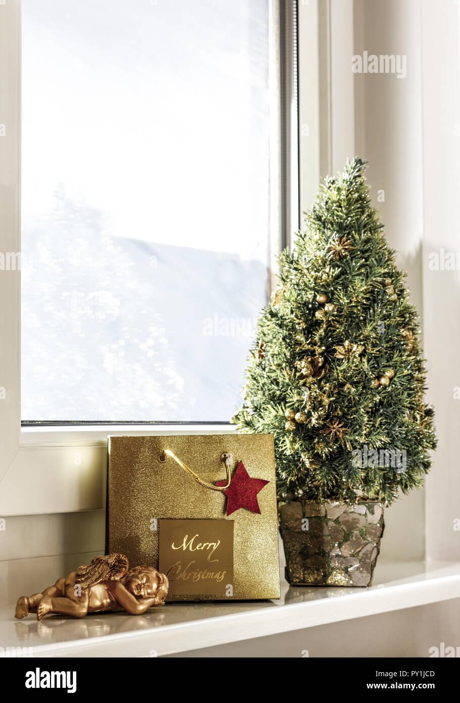 Weihnachtsdekoration mit kleinem Baeumchen auf Fensterbrett - Stock Image