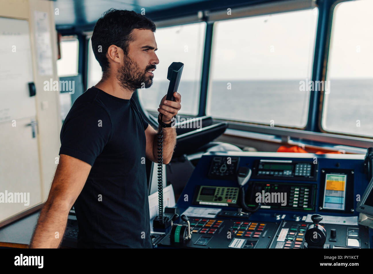 Marine navigational officer is reporting by VHF radio - Stock Image
