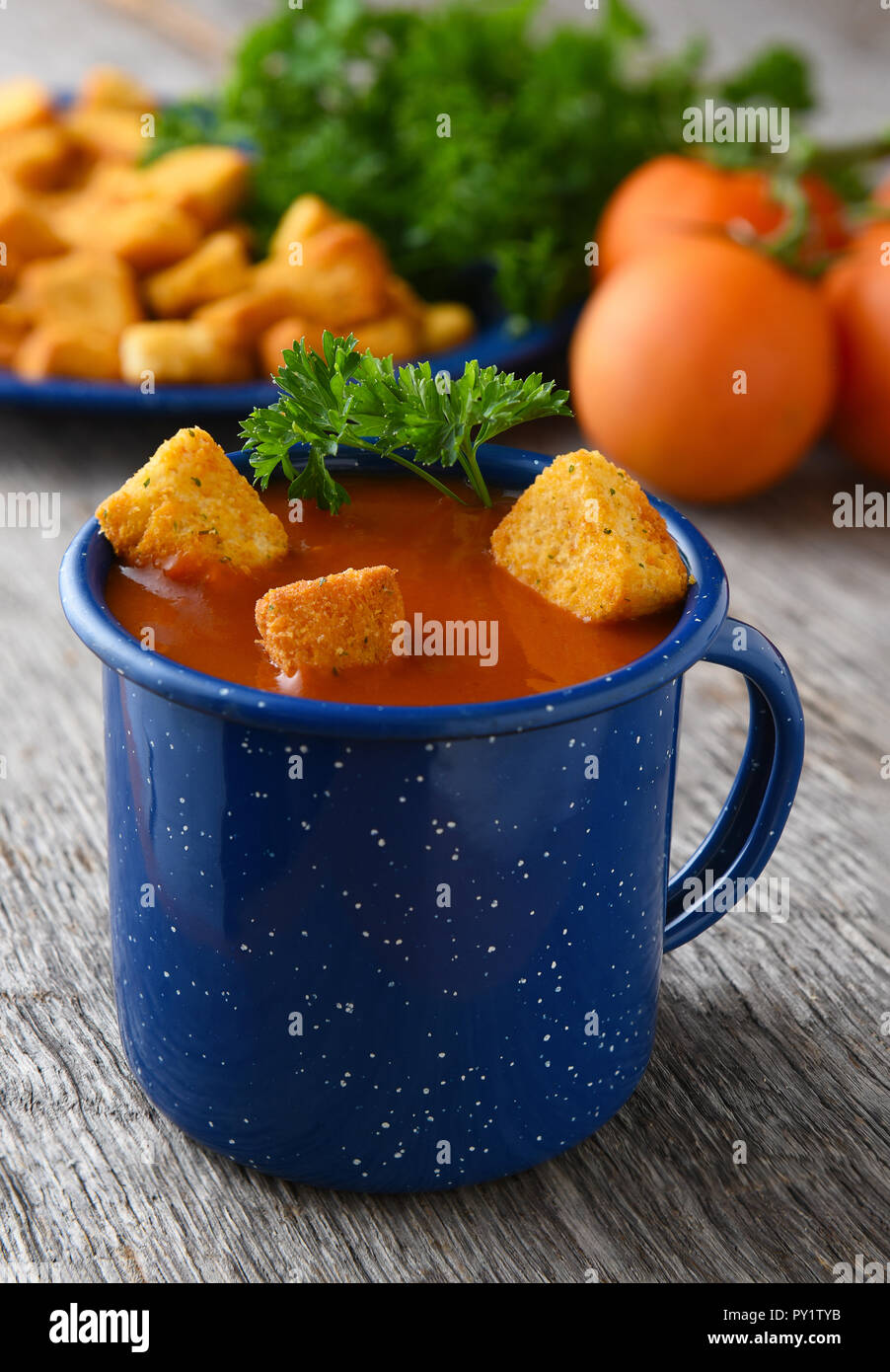 Closeup of a blue mug filled with fresh homemade tomato soup. Tomatoes, parsley and croutons out of focus in the background. - Stock Image