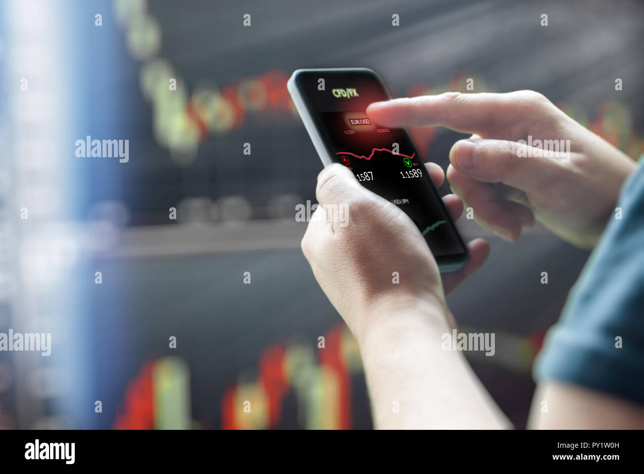 Mans hand holding mobile phone against dark stock market charts - Stock Image
