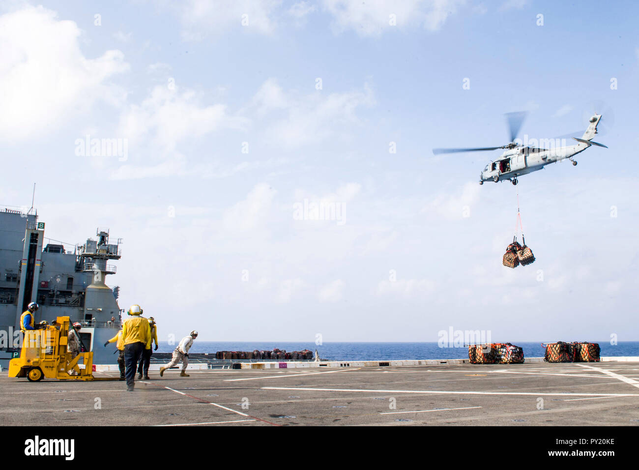 181021-N-PH222-1649 MEDITERRANEAN SEA (Oct. 21, 2018) Sailors assigned to San Antonio-class amphibious transport dock ship USS Anchorage (LPD 23) and Marines assigned to the 13th Marine Expeditionary Unit (MEU) participate in a vertical replenishment with dry cargo and ammunition ship USNS Medgar Evers (T-AKE-13) in the Mediterranean Sea, Oct. 21, 2018. Anchorage and embarked 13th MEU are deployed to the U.S. 6th Fleet area of operations as a crisis response force in support of regional partners as well as to promote U.S. national security interests in Europe and Africa. (U.S. Navy photo by Ma - Stock Image