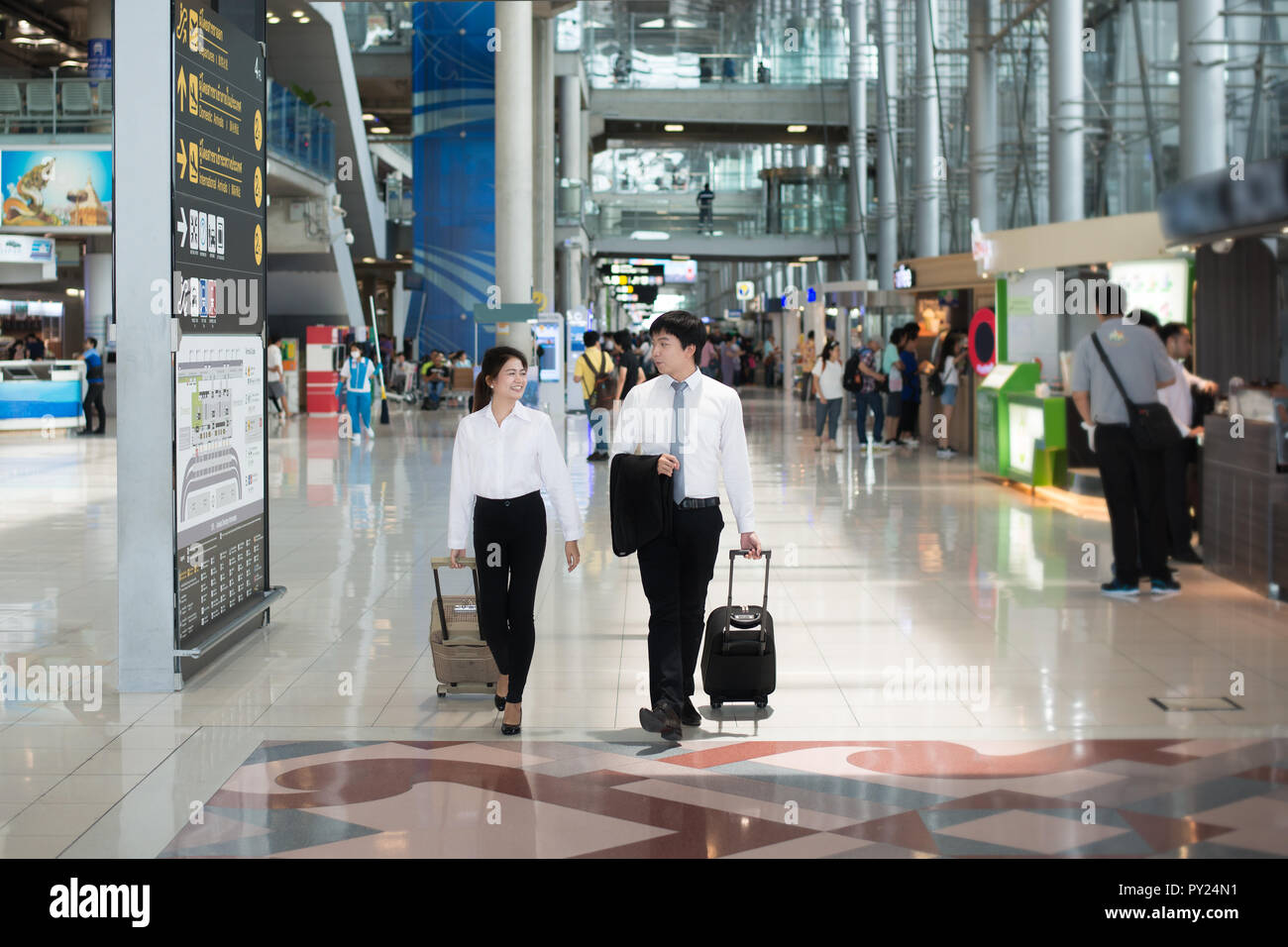 Portrait of Asian young happy couple business man and business woman with baggage walking and talking at terminal in airport. Business travel in airpo - Stock Image