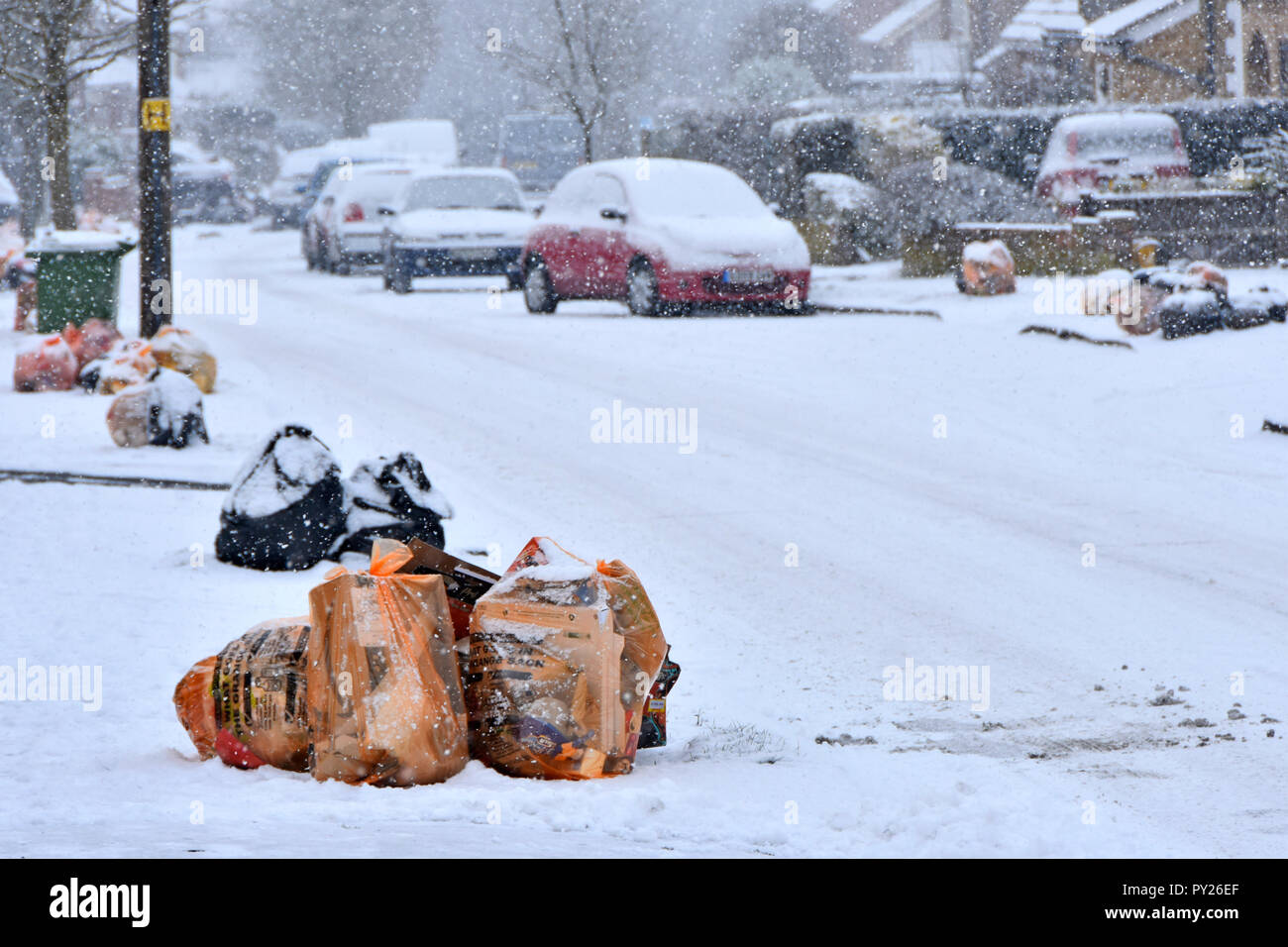 Winter street scene bags of recycle waste & black sack landfill rubbish snow covered on pavement for council waste management team collection truck UK - Stock Image