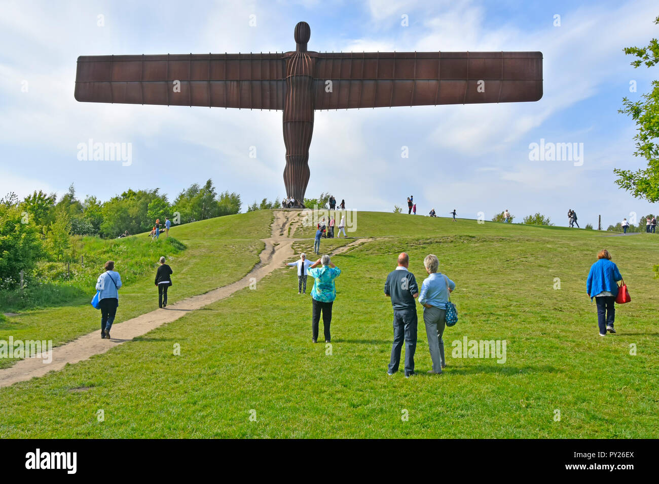 Rusty looking iconic Corten steel landmark sculpture Angel of the North by Antony Gormley people tourists posing & taking photos  Gateshead England UK - Stock Image