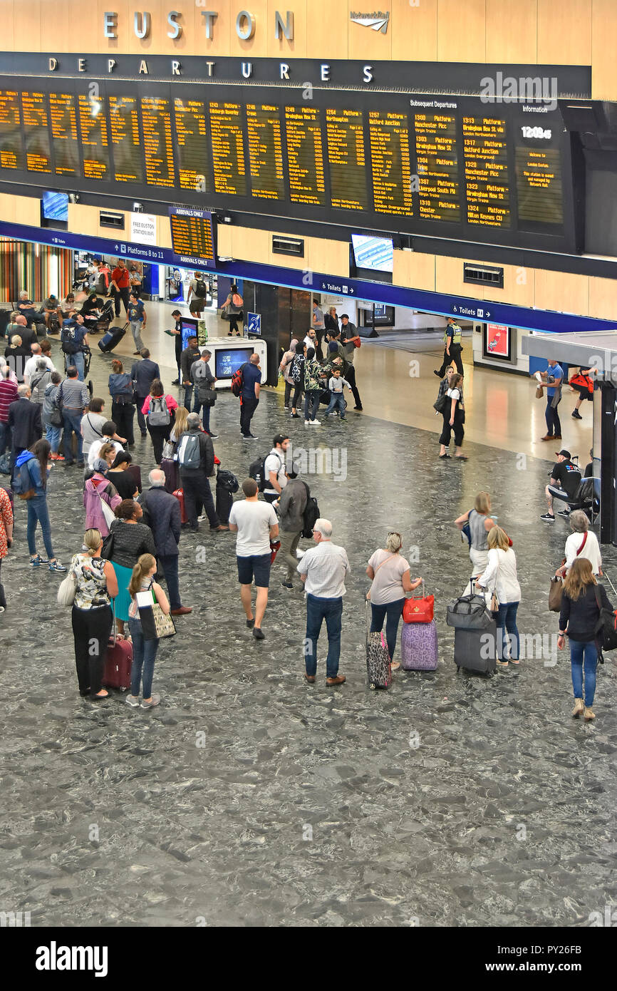 View from above looking down at interior of Euston railway station concourse with passengers viewing train departures travel information London UK - Stock Image