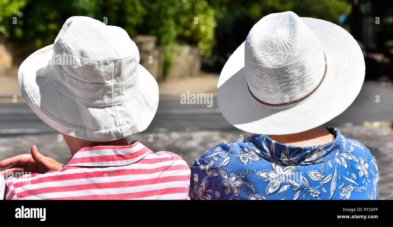 Two Senior mature women sit talking at bus stop on very hot 2018 heatwave summer day wearing white hat in midday sun Haworth West Yorkshire England UK - Stock Image
