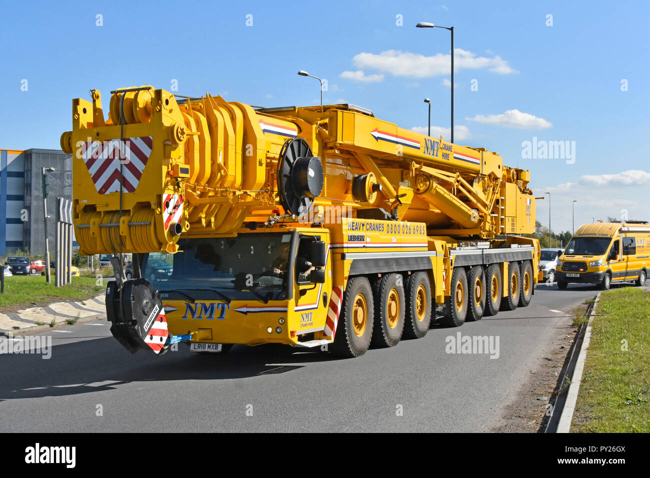 Hgv lorry truck driver in cab of left hand drive Liebherr telescopic hydraulic heavy lifting mobile crane driving on road Tilbury Essex England UK Stock Photo