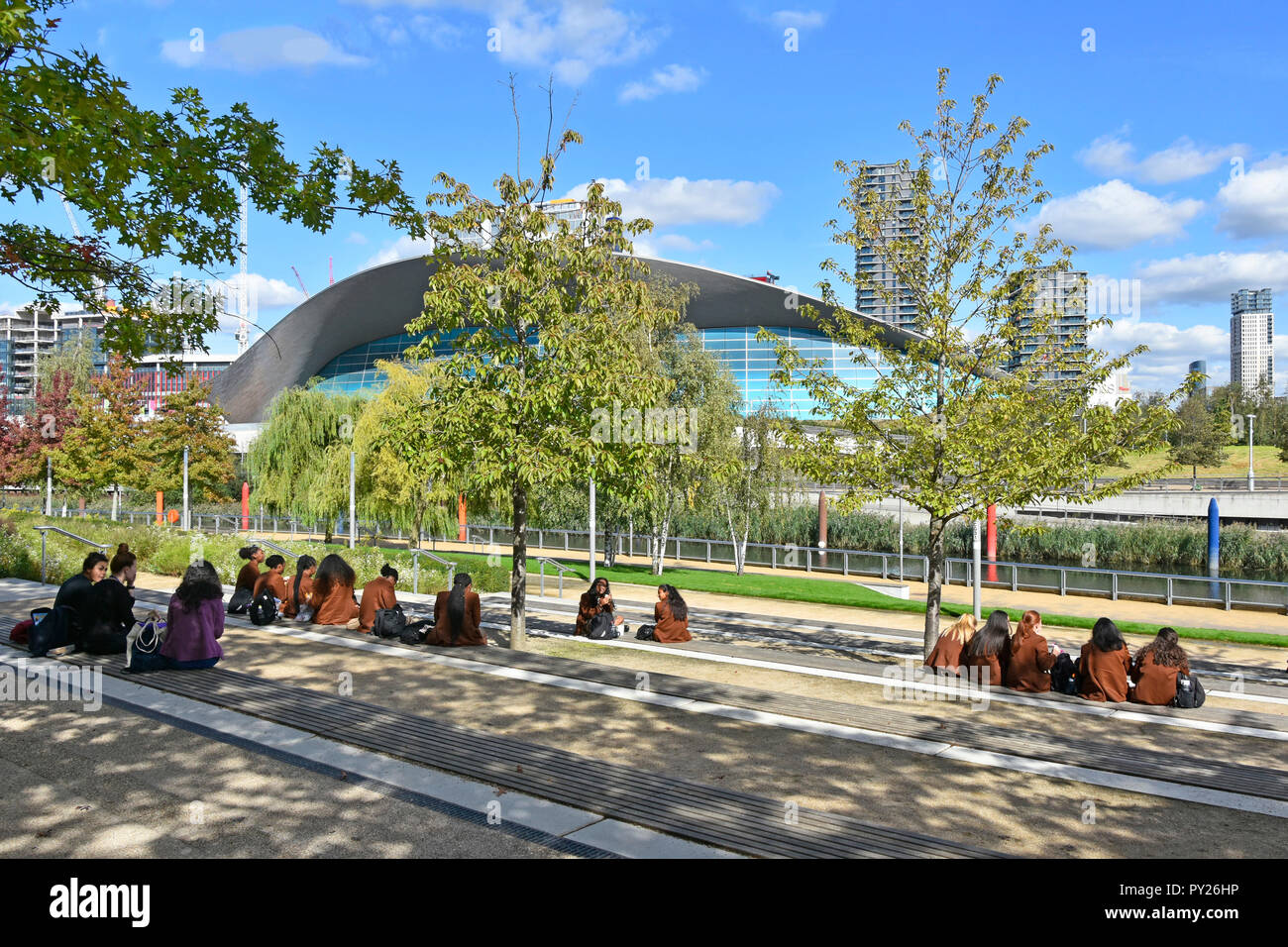 School children trip to Queen Elizabeth Olympic Park sitting for lunch break views of Stratford London Aquatics Centre Newham East London England UK - Stock Image