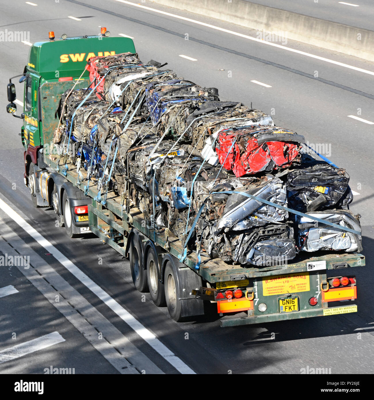 HGV lorry transport truck & articulated flat bed trailer driving along motorway heavy load of crushed cube scrap metal cars for recycling England UK Stock Photo