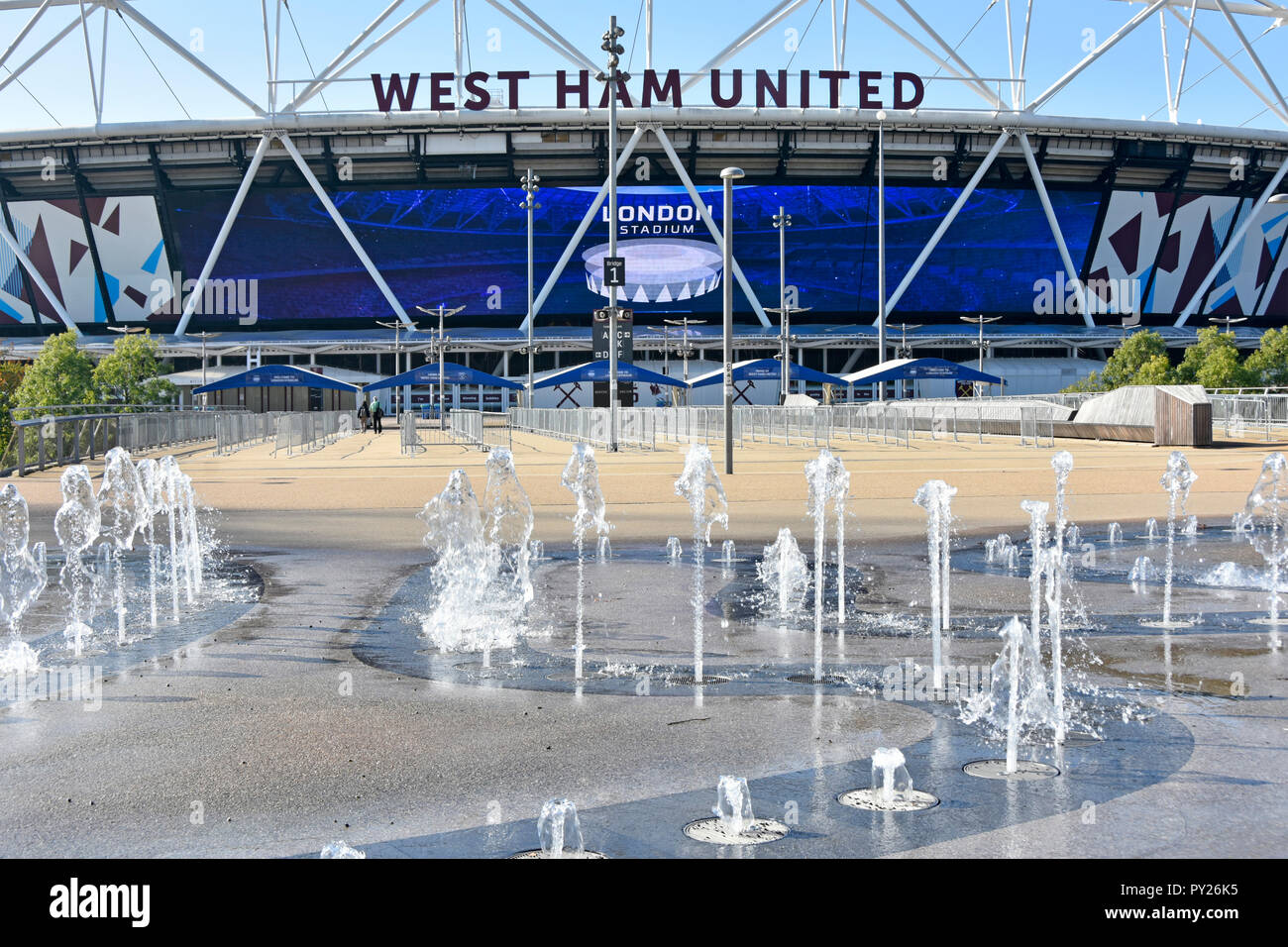 London Stadium sign on giant outdoor digital TV screen below West Ham United sign & play fountain in Queen Elizabeth Olympic park Stratford England UK - Stock Image