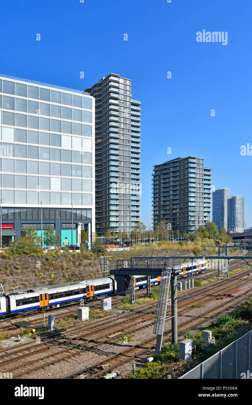 Transport for London tfl Overground suburban train on tracks between office & apartment development at Stratford & Olympic Park East London England UK - Stock Image