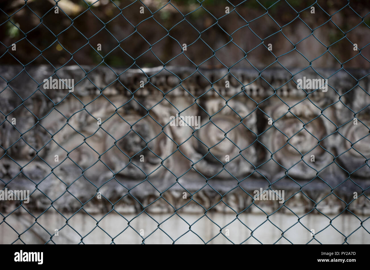 An Roman entablature carved in marble behind a wire fence, locked away for security. The entablature has not been restored and is lying on the ground. - Stock Image