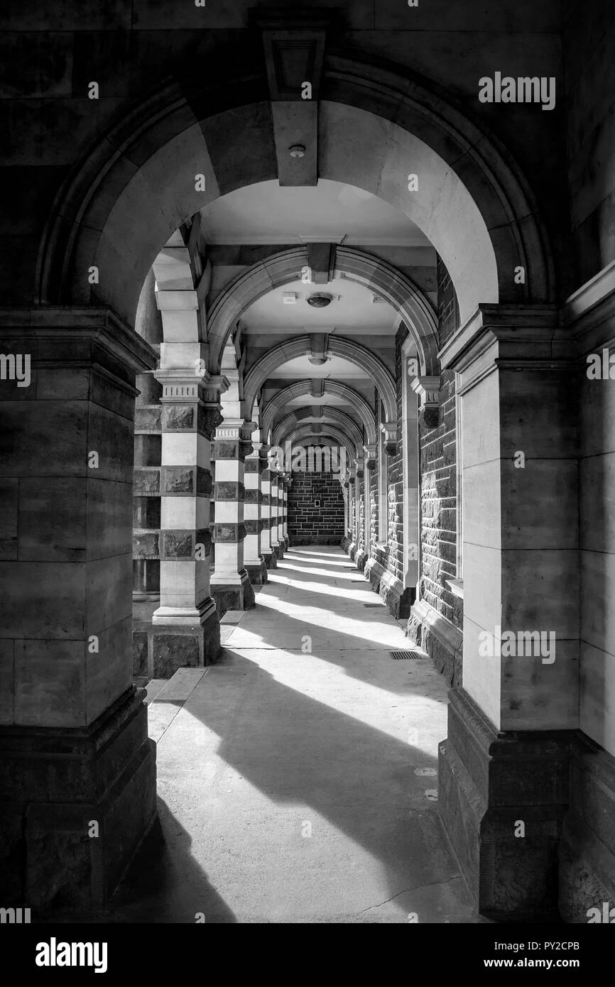 Archway in Dunedin, New Zealand that shows light and dark shadows, leading lines, with a hook in the centre of the image to rest your eye, fine art - Stock Image