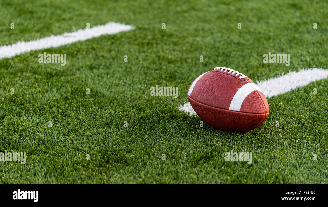 A brown leather American Football on a green artificial turf field - Stock Image