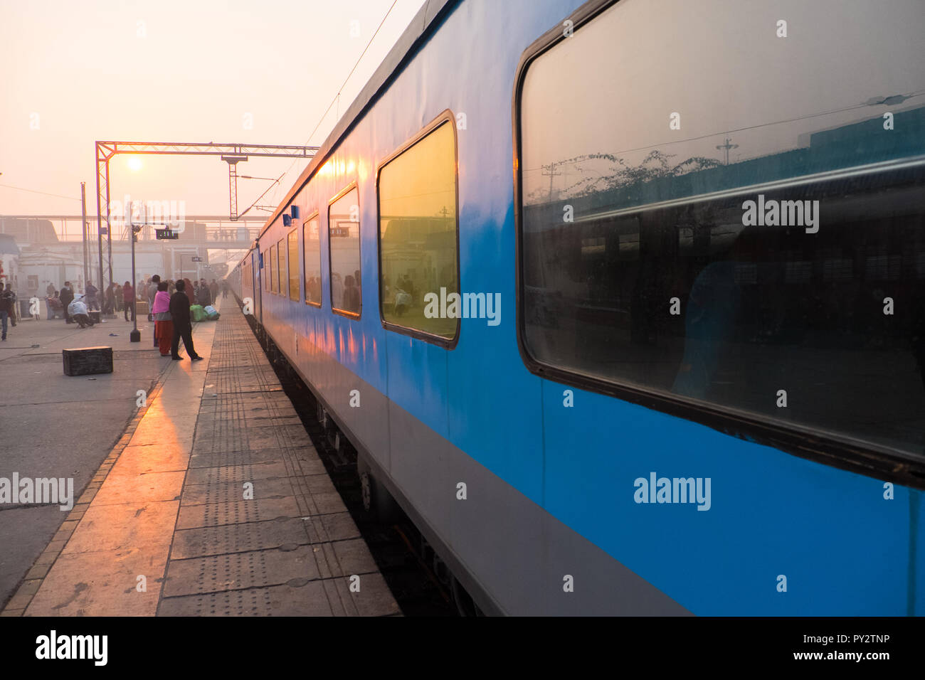 Indian railway station at dawn with Delhi-bound train at platform Stock Photo