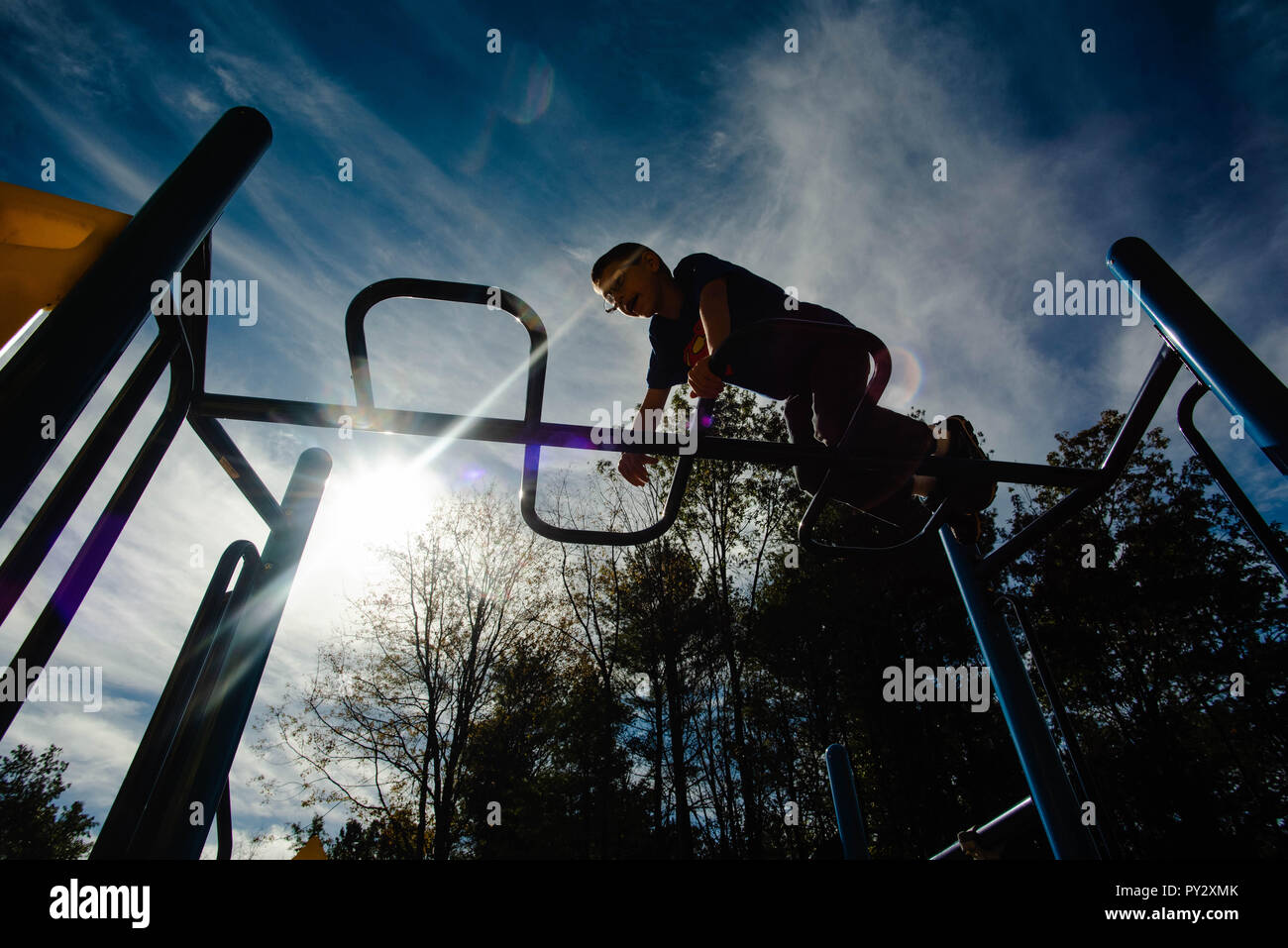 A 12-year old boy climbs across the monkey bars at a playground on a sunny day. Stock Photo