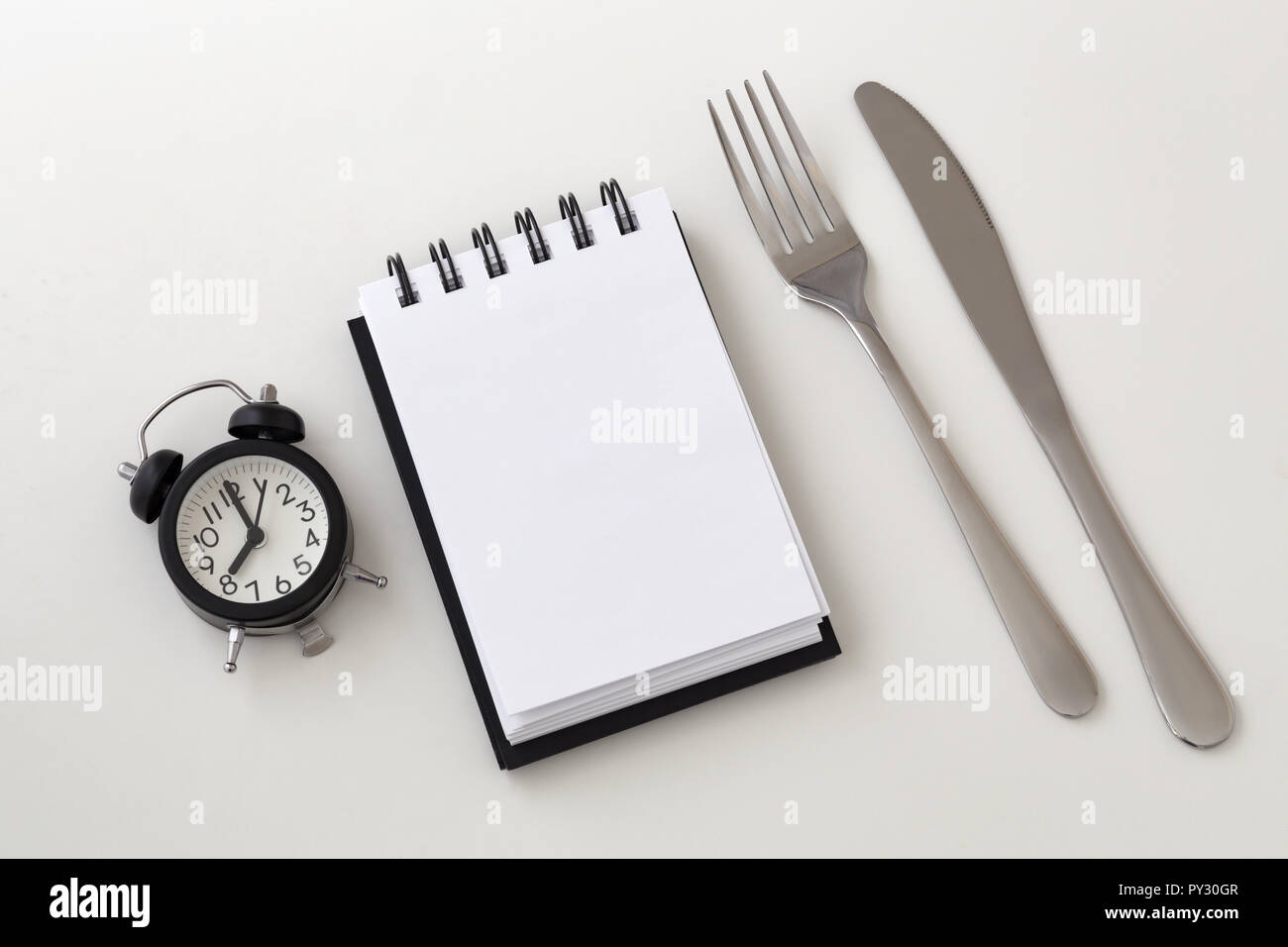 Clock and notepad with fork and knife, intermittent fasting and