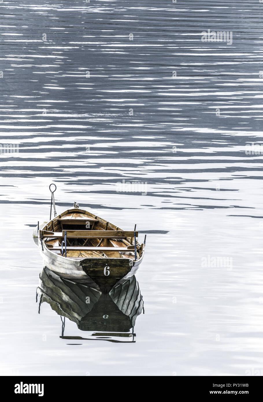 Ruderboot aus Holz schwimmt in ruhigem Gewaesser - Stock Image