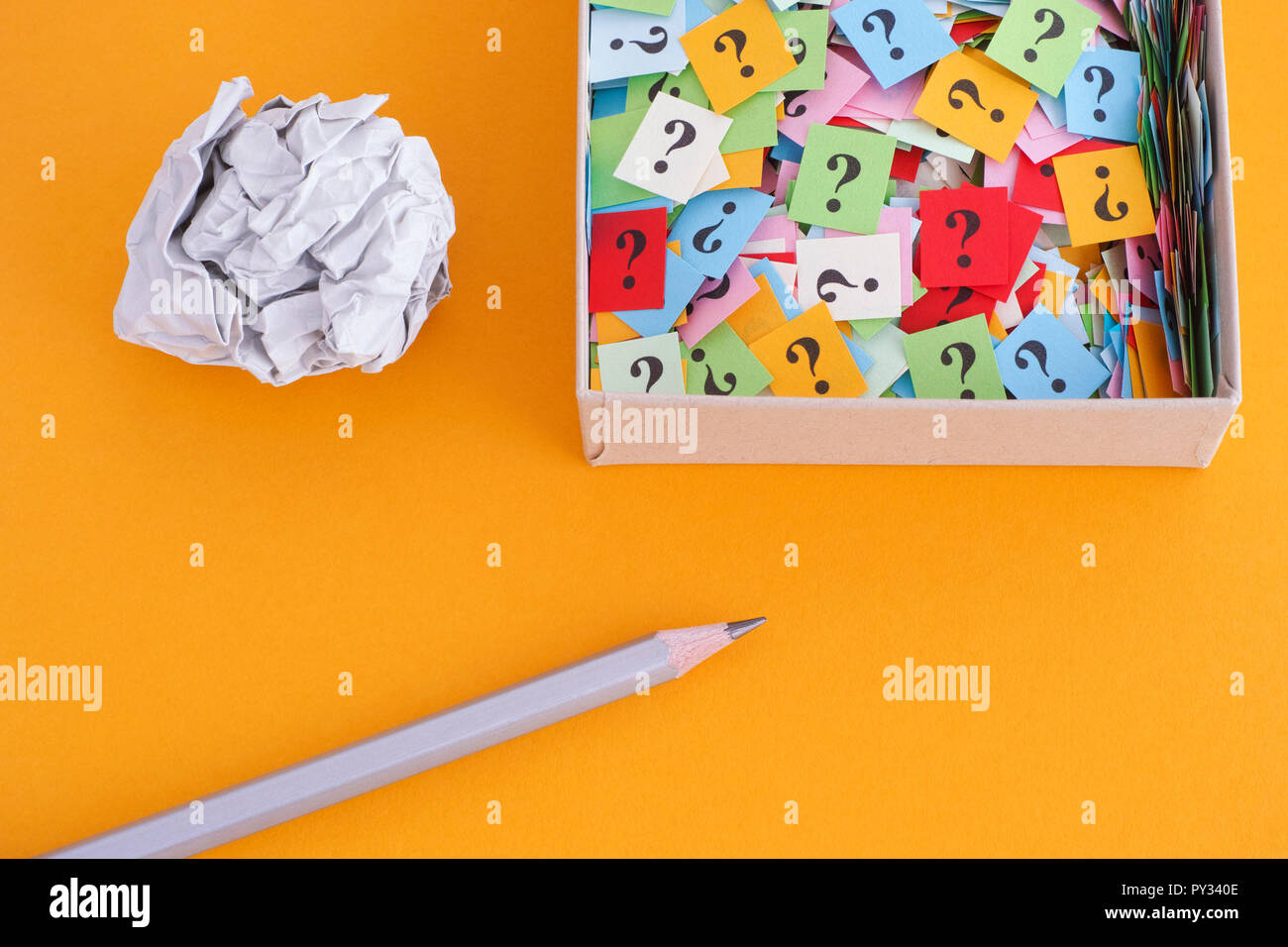 Pencil with crumpled paper ball and question marks in a paper box on yellow background. Concept image. Close up. Stock Photo