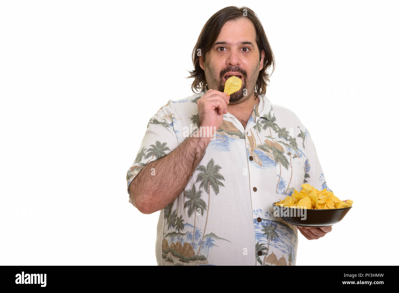 Portrait of fat bearded Caucasian man eating chips - Stock Image