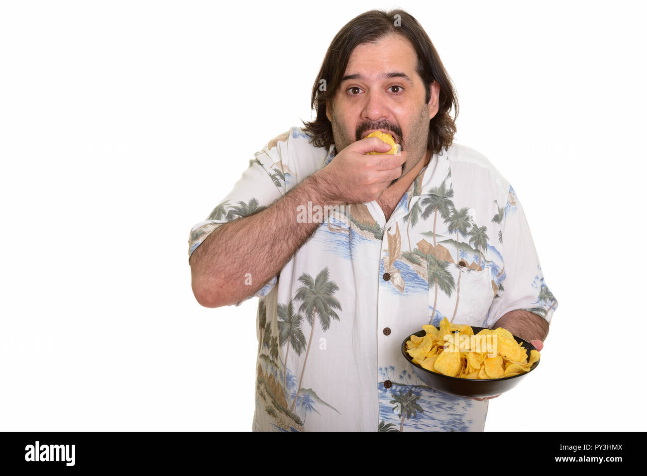 Fat Caucasian man eating mouthful of chips ready for vacation - Stock Image