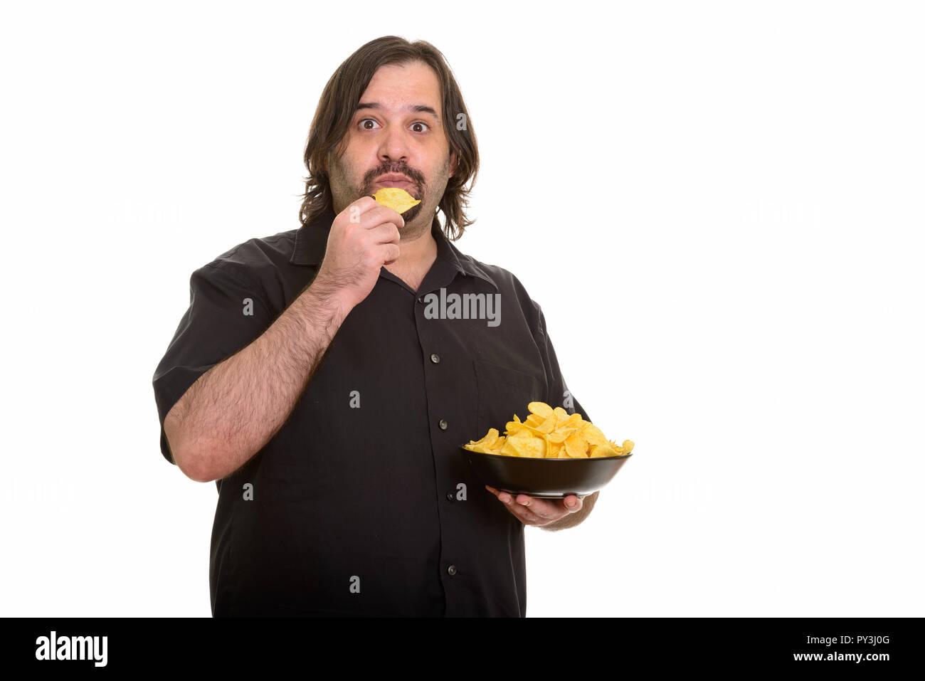 Fat Caucasian man eating bowl of chips - Stock Image