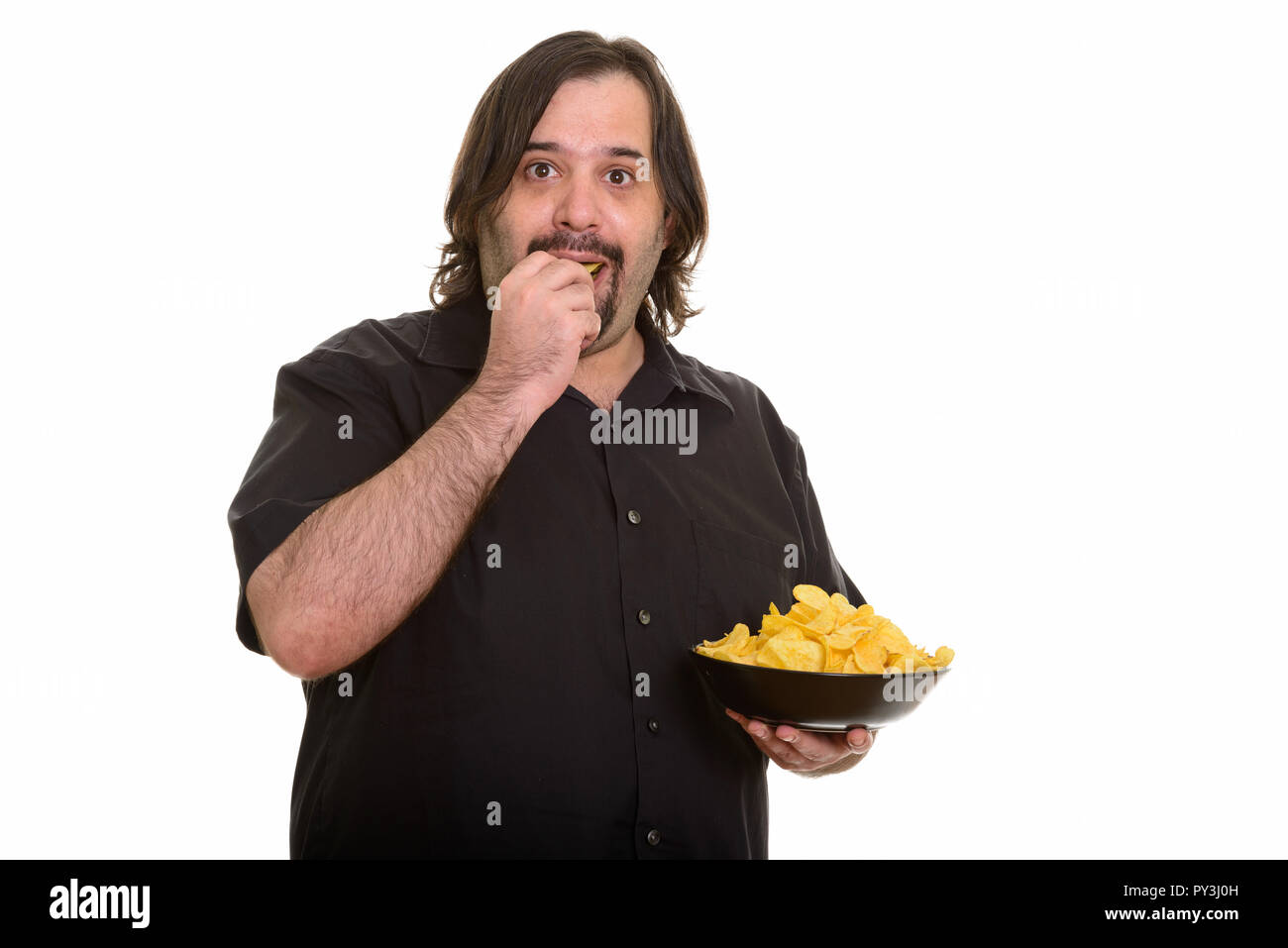Fat Caucasian man eating and holding bowl of chips - Stock Image