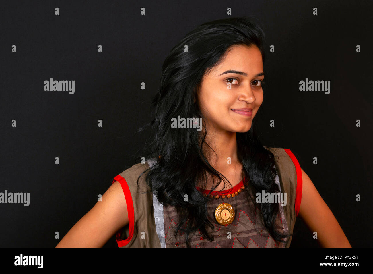 Happy young Indian woman smiling against black background, Pune, India. - Stock Image
