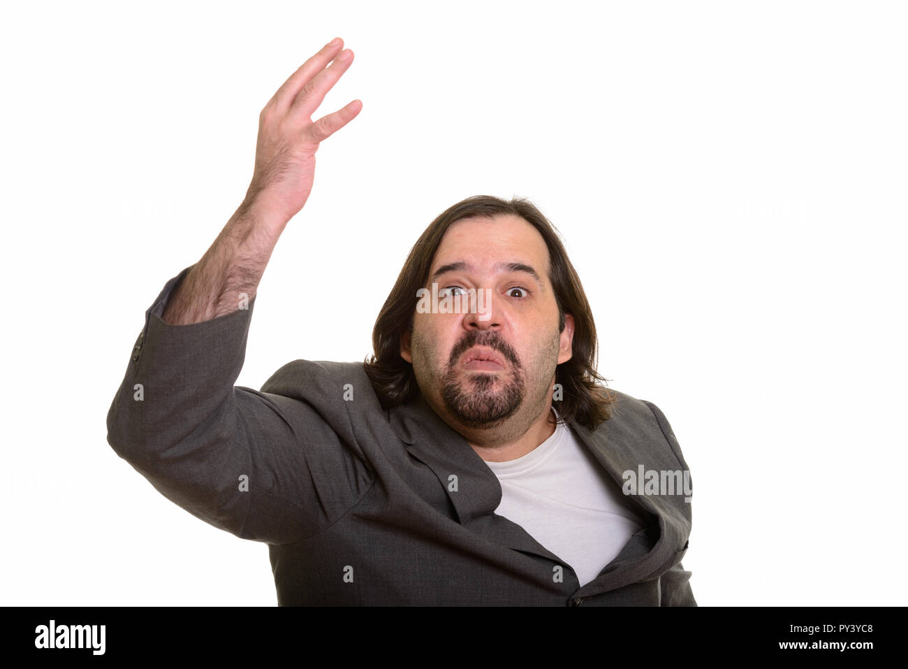 Portrait of angry fat Caucasian businessman raising arm - Stock Image