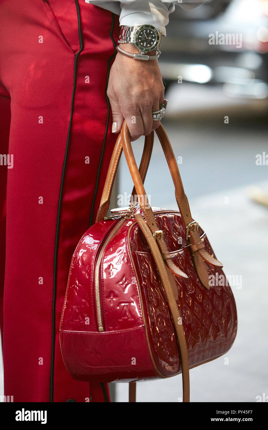 8344dff0fa14a0 MILAN, ITALY - SEPTEMBER 23, 2018: Woman with red Louis Vuitton bag and  green Rolex Submariner watch before Giorgio Armani fashion show, Milan  Fashion