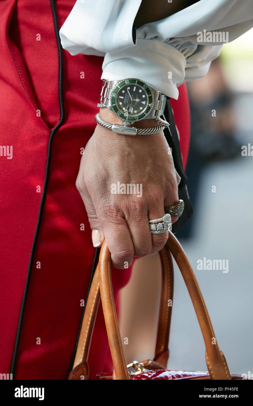 e84cd6bf0181fb MILAN, ITALY - SEPTEMBER 23, 2018: Woman with green Rolex Submariner watch  and red trousers before Giorgio Armani fashion show, Milan Fashion Week str
