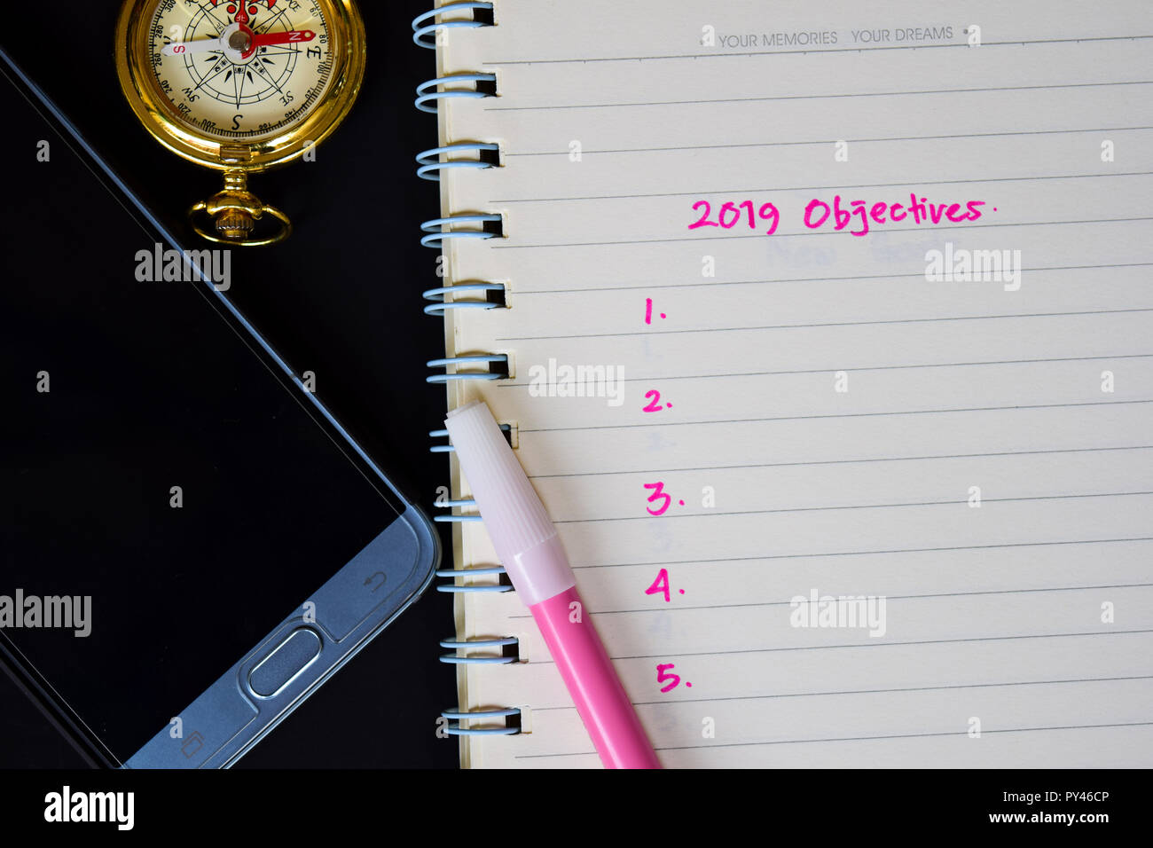 2019 Objectives text on notebook, compass, color pencil, smartphone on black background, for business presentation mock up for adding your list - Stock Image