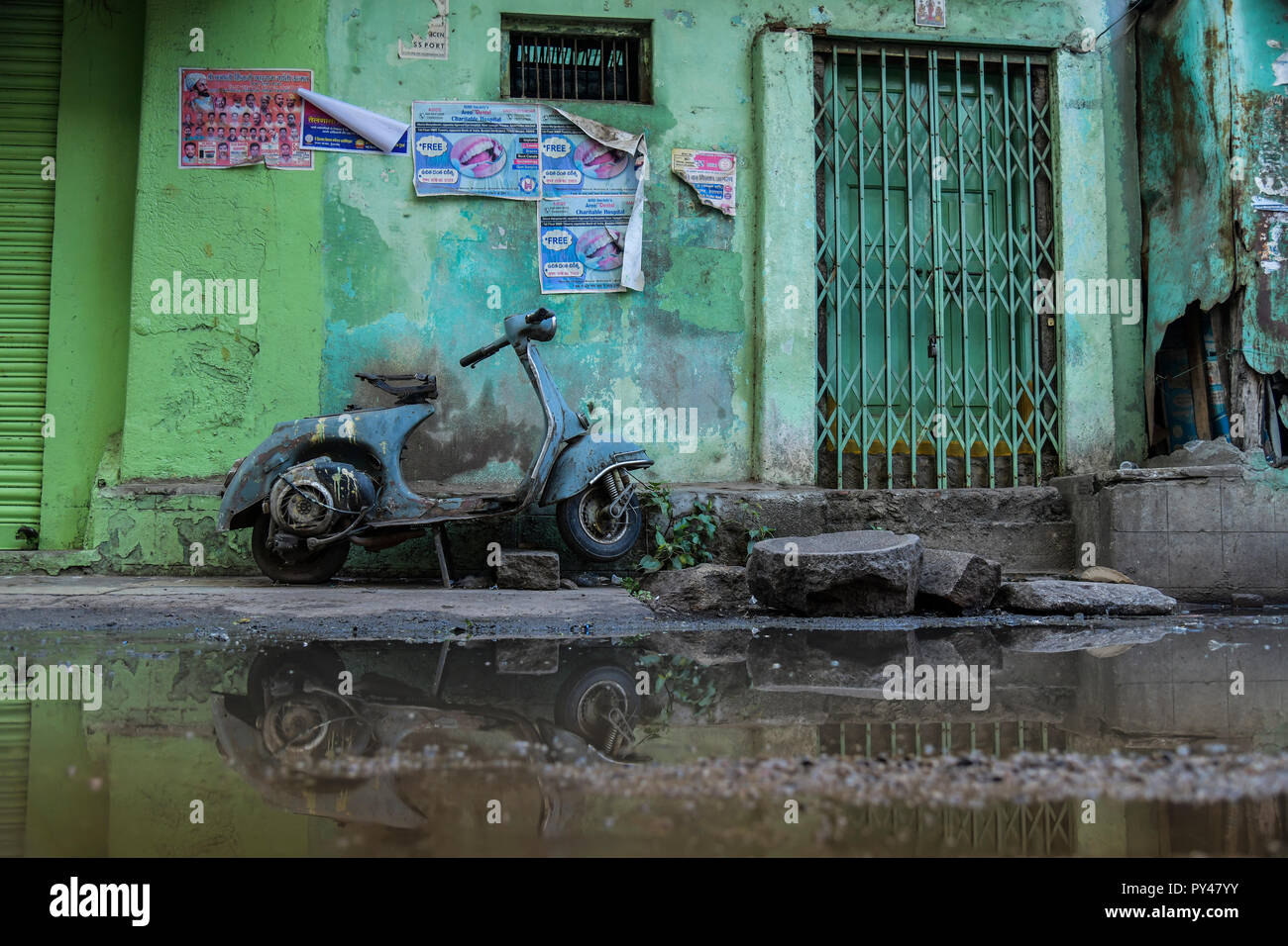 Antique scooter in stagnant water resulted this reflection thus making beautiful composition. - Stock Image