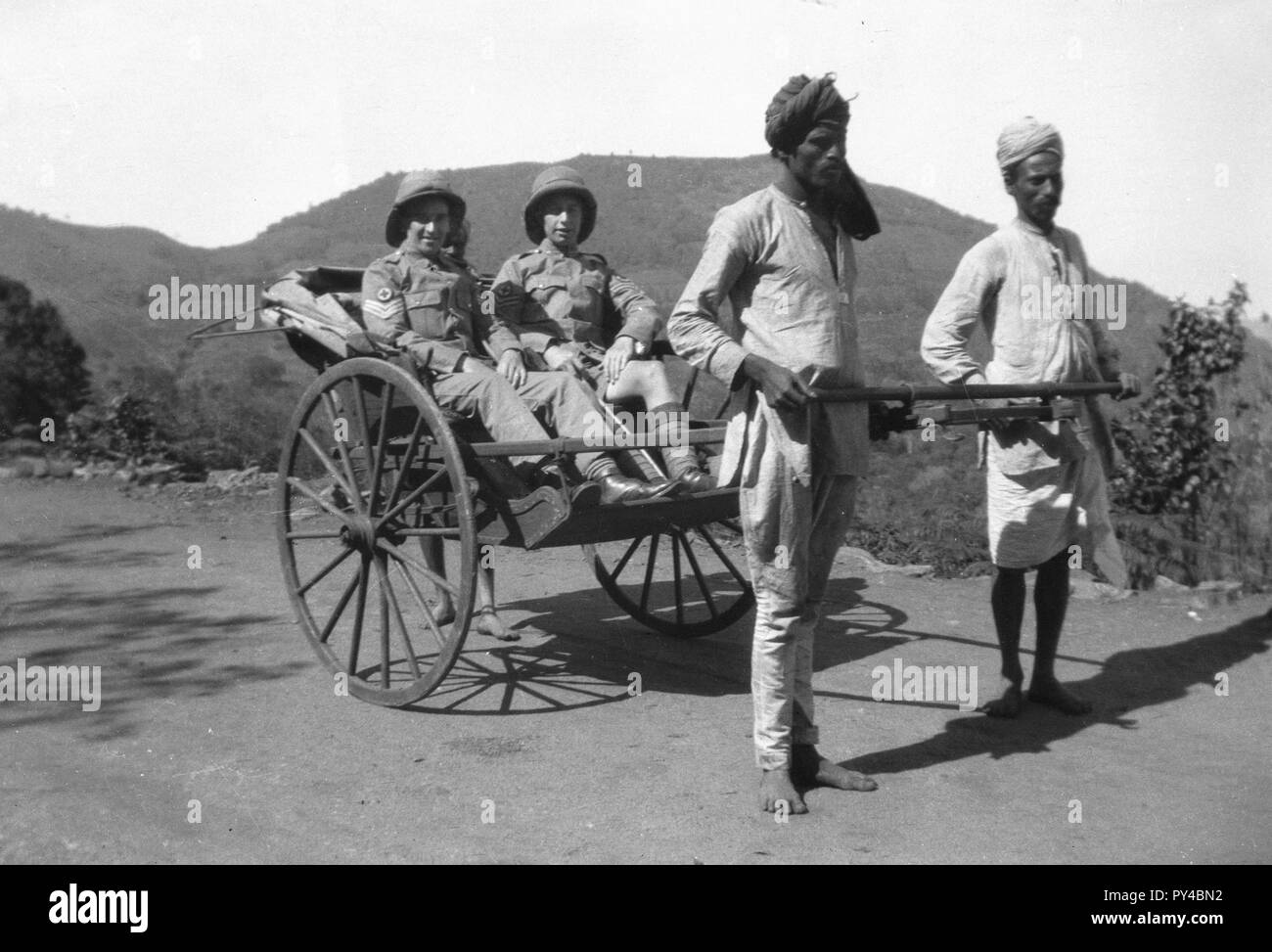 British Army Medical soldiers posing in a rickshaw tended by two Indian locals. India c1943  Photograph by Tony Henshaw - Stock Image