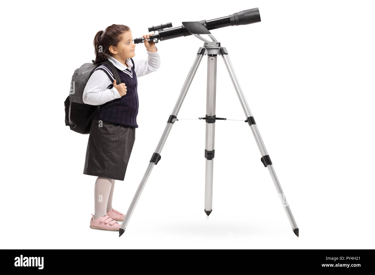 Full length shot of a schoolgirl in a uniform looking through a telescope isolated on white background - Stock Image