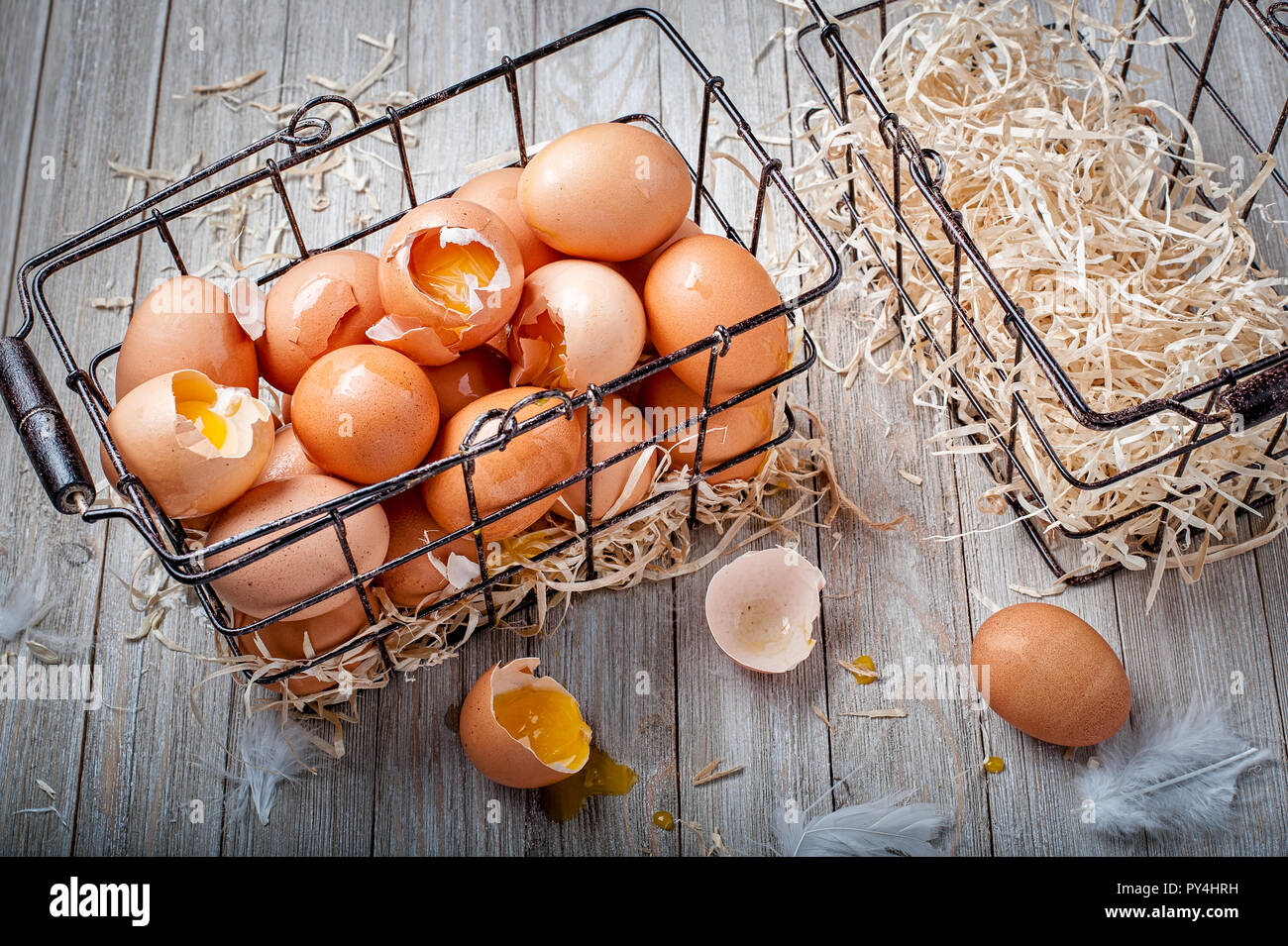 Visual metaphor/proverb: Don't put all of your eggs in one basket with cracked eggs. - Stock Image